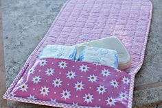 Diaper changing mat with holder for extra diapers and wipes. folds up into a small clutch