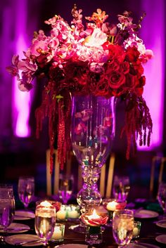 group of fuschia roses next to a group of plum tulips, eggplant mini cala lilies next to purple mokara orchids… The whole piece was finished with a cascade of fuschia hanging amaranthus and phalenopsis orchids spilling over the side of the vase