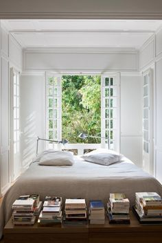 Books in a light bedroom with big white windows