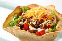 Weeknight Taco Salad recipe - Exactly what a time-crunched night calls for: a taco salad that includes an easy-to-make edible bowl. Cheese, tomatoes, lettuce and ground beef make a delish filling.