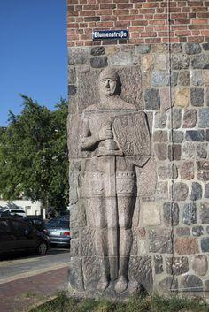 #Kiel Ein Wächter passt gut zu einem Polizeipräsidium. Das plastisch ausgebildete Relief einer Rolandsfigur mit Schild, Schwert und Rüstung wurde in die Außenmauer des repräsentativen Backsteinbaus für d...