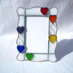 Lots of hearts in every color of the rainbow; just for you. Children love rainbows and love to be loved. This stained glass picture frame combines both of those. There are lots of hearts on it to show your love in many ways. Put your little ones picture in this frame and give it to Gramma. She loves rainbows and hearts too. I made this adorable stained glass picture frame to hold a 4 x 6 photo. 6 hearts in rainbow colors decorate the white opal glass frame. The hearts are clear cathedral…
