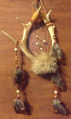 This dream catcher is made with 2 deer antlers has artificial sinew webbing with carved bone beads in the web  has buckskin hanger at the top And coyote fur attached at the bottom Has pheasant feathers attached with glass beads on the buckskin along with stone and carved bone beads   measures 8 inches wide and total length is 18 inches has a total of 5 points