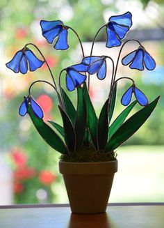 These stained glass potted bluebells make such a wonderful addition to any home or garden decor. This bluebell arrangement is made from Spectrum glass, well known for its unusual colors and striking clarity. Sadly the Spectrum Glass Company is closing, soon we will be completely out of this glass and will not be able to create more of this piece in this color. The striking steel blue flowers are complimented by dark and light green leaves. Mounted in a aged pot set in stone it is sure to ...
