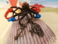 One dead pirate, one poisonous arrow, and one all-knowing Kraken, King of the Sea, who sees all. Does he know where the pirate hid his bounty? This cool bracelet features an antique bronze large Octopus, bronze Pirate and Arrow and blue and orange waxed cotton cording. Kraken Steampunk Pirate Bracelet by ZodiacGirls, $7.49