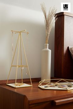$25 · Looking for a storage solution to hang masks, necklaces and more? Look no further than Prisma Jewelry Stand. The metal wire with a modern matte brass finish has been shaped into a narrow pyramid shape and has spokes on the top, intended to hang jewelry on. This piece makes excellent use of vertical space for storing accessories, but also can add a dynamic layer of height to a collection of decorative items on your vanity, countertop or dresser top in your bedroom or bathroom.