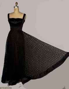 "SHANNON RODGERS EVENING GOWN, c. 1948  Go Back        April 17, 2013 - NEW YORK CITY      New York City    Black silk satin sheath, silk organdy honey-comb pattern overskirt, B 38"", W 29"", L 59"", (tear to 1 honey-comb near hem) very good. Augusta Auctions"