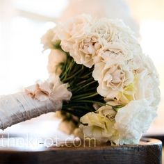 an arrangement of ivory and white roses, sweetheart roses and lisianthus. The exposed stems were wrapped neatly with a silk ribbon.