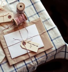 wrapped package : brown paper . bakers twine . craft tag . on blue-lined tablecloth