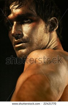 Dramatic portrait of intense looking shirtless male model in bronze and gold makeup turning by CURAphotography, via ShutterStock