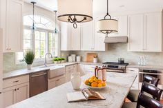 Despite the large window, the kitchen was extremely dark with cherry-stained cabinets and red walls before designer Lisa Furey renovated the space. The layout is kept the same, but everything is lightened up.White Shaker cabinets combine with limestone countertops and glass tile backsplash for a clean, transitional look.