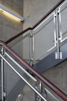 At Concordia University School of Pharmacy, two large stairways feature stainless steel woven wire mesh infill panels mounted using glass clips. Steel Stair Railing, Staircase Railing Design, Modern Stair Railing, Staircase Handrail, Home Stairs Design, Modern Stairs, Balcony Glass Design, Balcony Grill Design, Balcony Railing Design