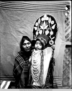 Sabina Minthorn and babe.  Cayuse A Native American woman, identified as Sabina Minthorn of the Cayuse tribe, holds her baby in a cradleboard. The woman wears a headscarf and a shawl. The cradleboard includes an embroidered floral motif, beadwork, and leather fringe.  Photo by Major Lee Moorhouse