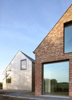 Atelier Tom Vanhee adds gabled wooden extensions to brick farmhouse