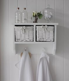 A white wall shelf with 2 baskets and hanging pegs. New England style ideas for living room, bathroom and bedroom furniture