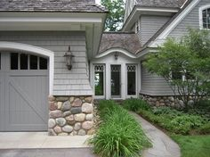 Stone on bottom of garage. Arched doors.  Love this style door.