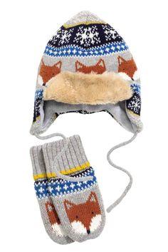 Czapka i rękawiczki: Komplet z żakardowej dzianiny z domieszką bawełny składający się z czapki i rękawiczek z jednym palcem. Czapka z przyszytym podwinięciem z imitacji futra, nausznikami, wiązaniem pod brodą i pomponem u góry. Rękawiczki z szerokim ściągaczem u góry. Czapka i rękawiczki z dżersejową podszewką.