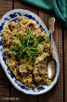 Risotto with dried porcini mushrooms topped with fresh arugula and parmesan