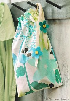 DIY Tea Towel Drawstring Bag Craft from Gooseberry Patch. Made for moms this easy DIY bag holds everything!