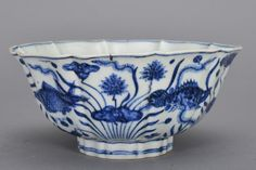 A BLUE AND WHITE FISH BOWL, Ming period. The bowl is concave-shaped. The exterior is decorated with numerous fishes surrounded by sea landscape. The base of the bowl is decorated with six Chinese characters. 8 3/8 in. diameter, 3 11/16 in. tall.