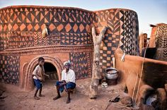 An adult and a child look out from the front of their home in Tiebele, the painted village of the Gurunsi people in southern Burkina Faso.