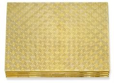 A GOLD AND SILVER-GILT VANITY CASE, BY CARTIER ~ The rectangular case of engraved woven-design opening to reveal a fitted mirror, three glazed compartments, a tortoiseshell hair comb, a money clip and a lipstick holder, circa 1960,