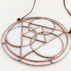 """Sacred geometry triangle mandala in a milky white iridescent and clear textured iridescent stained glass with copper patina. Measures 7.5"""" round and can be hung with the attached faux suede cording. F"""
