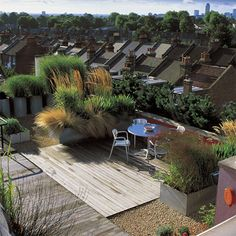 This roof terrace combines gravel, decking and modern containers with grasses.  It is probably only used during the Summer as the planting would be pretty dreadful any other time of the year!