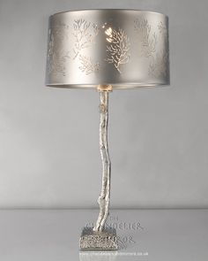 "Rowan - Table Lamps, This striking, muted silver table lamp has a tree stem with a metal leaf detail, cut out design shade. Quirky, unusual and a real ""Head Turner""!"