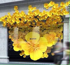 Apple store shop window display using flowers spelling into the facade Spring Window Display, Window Display Retail, Display Windows, Retail Displays, Shop Displays, Paper Flower Backdrop, Paper Flowers, Vitrine Design, Window Display Design