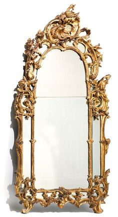 Beautiful beading mirror gilded wood richly carved with scrolls, foliage and scrolls fillets topped with winged dragons. The pediment decorated with olive branches on one side and oak on the other. In the center, a large jagged asymmetrical shell with acanthus leaves topped with a cocoa bean. Start of Louis XV.
