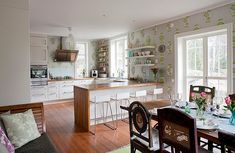 Elegant wallpaper unites the kitchen with the dining and living space visually