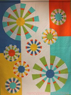 "Fun ""Twirling Parasols"" quilt with white segments mixed in with the colors! Quilt by Nancy Zieman."