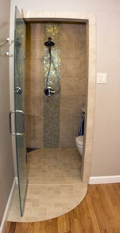 Closet turned wetroom for very small guest ensuite. Oceanside Tessera mosaic glass tile in iridescent Sandstone. Crossville Strong shower wall tile in Almond. Delta In2ition removable shower head. Toto Aquia wall hung toilet. American Standard Ravenna wall hung sink. By J.T. McDermott Remodeling.