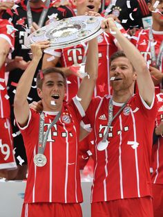 Philipp Lahm and Xabi Alonso of Bayern Muenchen lift the Championship trophy in celebration of the 67th German Championship title following the Bundesliga match between Bayern Muenchen and SC Freiburg at Allianz Arena on May 20, 2017 in Munich, Germany.