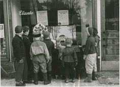 Lapsia katselemassa Elannon leipämyymälä Leipä-aitan Satuikkunaa   Tuntematon 1955   Helsingin kaupunginmuseo   Lapsia katselemassa Elannon leipämyymälä Leipä-aitan Satuikkunaa. Ikkunassa kaksi ilmoitusta: Arvauskilpailu lapsille, Gissningstävling för barn. -- vedos, paperi, mv