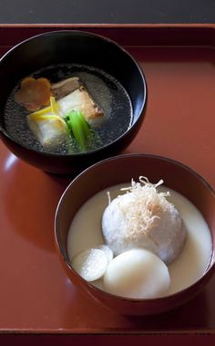 At rear is Kanto-style zoni with square mochi, chicken, kamaboko fish cake, komatsuna mustard spinach, daikon, carrots, and yuzu citron in a seasoned dashi broth. In the foreground is Kansaistyle zoni with round mochi, ebiimo taro, daikon, and shavings of dry-cured bonito in a white miso soup.