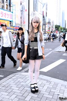 20-year-old Maiko on the street in Harajuku with pastel hair, an H&M cardigan over a striped top with a bustier, faux leather shorts, white tights, and WEGO platform sandals. Her cute pin is the first we've seen of the brand new HEIHEI Dalmatians collection on the street.