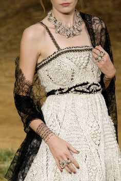 white crochet gown and a sheer black lace shawl