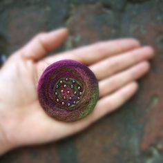 I created this pin by needle felting variegated plum and leafy green wool into a freeform circle. I then sewed tiny glass teardrop shaped beads in the center and sewed a one inch pinback on the reverse. Size: This pin is about 2.25-2.5 inches across. These pins are made to