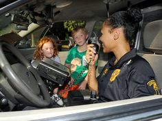 Ames Police Offcer Ny Saadiq talks on the radio as she shows off the inside of a police car to Tate Esser, 7, and his sister, Tessa, 5, during the National Night Out crime prevention event at Brookside Park on Tuesday in Ames. Photo by Nirmalendu Majumdar/Ames Tribune