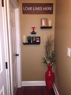Cute idea to decorate the end of a hallway. Floating shelves, large vase, picture frames and candles
