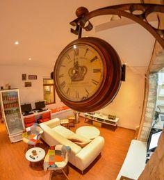 Sala de estar do hotel com um relógio antigo pendurado, uma geladeira de esposição e dois computadores