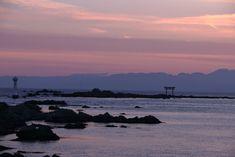 暮れなずむ海。たたずむ燈台と鳥居。