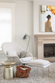Neutral living room with gold stool, modern lamp, and neutral lounge chair
