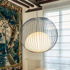 """Suspension """"Nour"""" de la designer Julie Pfligersdoffer. C'est un luminaire d'acier laqué et de verre soufflé. Signifiant lumière en arabe, Nour est née de l'idée de capturer la lumière dans une cage suspendue. Cette cage, de forme ronde se compose de 60 fils d'acier soudés par des anneaux de métal."""
