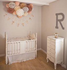 une chambre de bebe aux murs gris avec un lit bebe vintage blanc et des pompoms en tete de lit couleurs peche taupe ecru