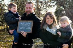 happy family holiday photography, smiling with Merry Christmas sign