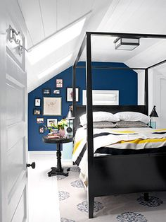 Hodges turned what had been an upstairs sitting area into the master bedroom, adding a closet for storage. The ceiling gained character courtesy of wood planks and updated skylights. Whitewashed floors and one bold wall (painted Benjamin Moore's Blue) offer dramatic contrast. #countryliving #bedrooms