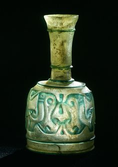 Bottle, colorless glass, with relief-cut decoration in a green overlay,   Iraq or Iran; 9th-10th century